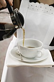 Chambermaid pouring coffee into cup