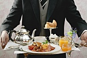 Butler serving English breakfast on tray