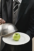 Butler serving apple on plate with dome cover