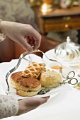 Hands serving sweet pastries and scones to eat with tea