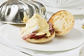 Eggs Benedict on plate with dome cover