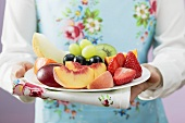 Woman serving a plate of fresh fruit