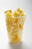 Pineapple chunks in a plastic beaker