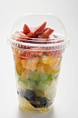 Fruit salad with strawberries in a plastic beaker
