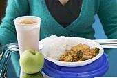 Frau hält Tablett mit Tofugericht, Apfel und Getränk