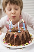 Small boy blowing out candles on birthday cake