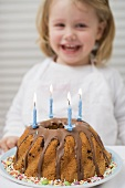 Small girl behind birthday cake with candles