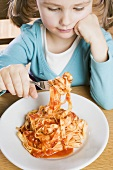 Girl eating ribbon pasta with tomato sauce