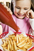 Girl putting ketchup on chips