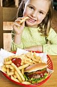 Girl eating chips with ketchup and hamburger