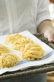 Person holding home-made pasta on wicker tray