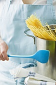 Woman holding kitchen spoon and pan with spaghetti