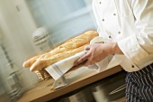Chef hurrying through kitchen with baguettes