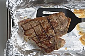 Grilled T-bone steak on aluminium foil with spatula