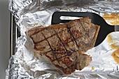 Grilled T-bone steak on aluminium foil with spatula