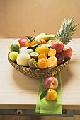 An assortment of fresh fruit in a basket on a wooden table