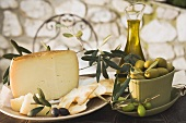 Olives, cheese, crackers & olive oil on table out of doors