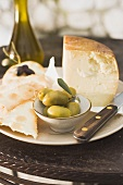 Cheese, green olives, crackers and olive oil on table
