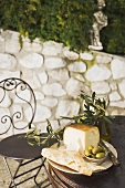Cheese, green olives, crackers & olive oil on outdoor table