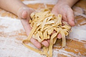Child's hands holding home-made ribbon pasta