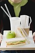 Frau hält Tablett mit Sandwiches, Apfel und Getränk