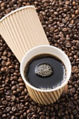 Black coffee in paper cup on coffee beans