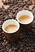Two cups of espresso on coffee beans