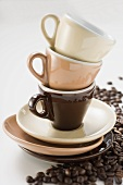 Three espresso cups and saucers, stacked, coffee beans