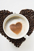 Cup of cappuccino with cocoa powder heart on coffee beans