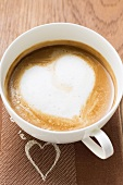 Cup of coffee with milk froth in shape of heart (overhead)