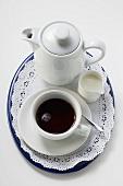 Black coffee in white cup, cream, coffee pot