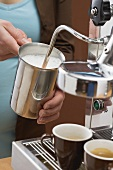 Woman frothing milk with espresso machine