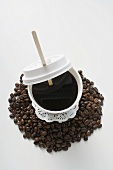 Black coffee in plastic cup on coffee beans