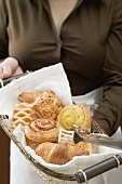 Woman in apron holding basket of sweet pastries