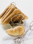 Toast in toast rack, croissant and pastry tongs