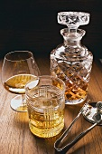 Cognac & whisky in glasses & carafe, ice tongs beside them
