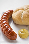 Sausage (bratwurst) with mustard & bread roll on paper plate