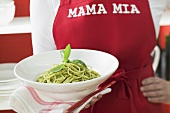 Woman in red apron holding plate of spaghetti with pesto