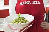 Frau mit roter Schürze hält Teller Spaghetti mit Pesto