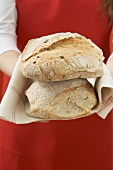 Woman holding two freshly baked loaves of bread