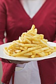 Waitress serving plate piled high with chips