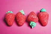 Sugar strawberries on red background
