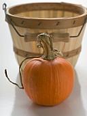 Orange pumpkin in front of woodchip basket