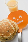 Pancakes for Halloween with spatula & glass of orange juice