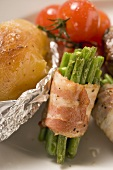 Bacon-wrapped beans, baked potato and cherry tomatoes
