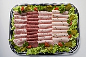 Cold cut platter garnished with gherkins (overhead view)