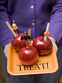 Woman holding tray of toffee apples for Halloween