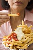 Woman eating chips with ketchup and mayonnaise