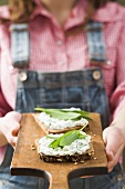 Person holding wholemeal bread with quark & ramsons on board
