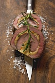 Two slices of stuffed beef roulade with rosemary